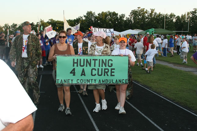 women holding a sign while walking on a track