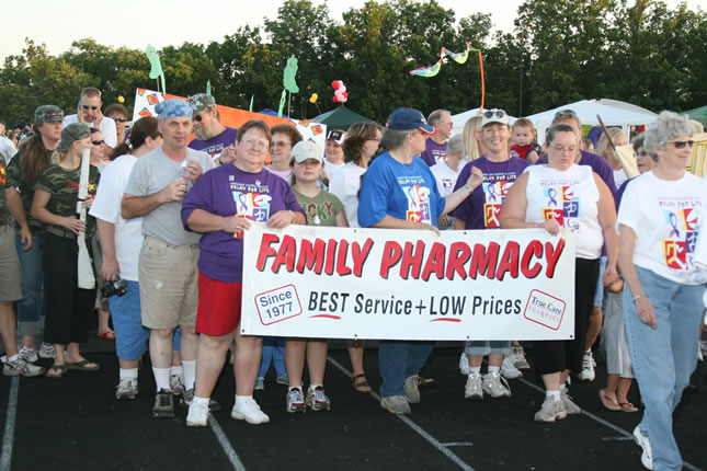 crowd walking on track holding family pharmacy sign